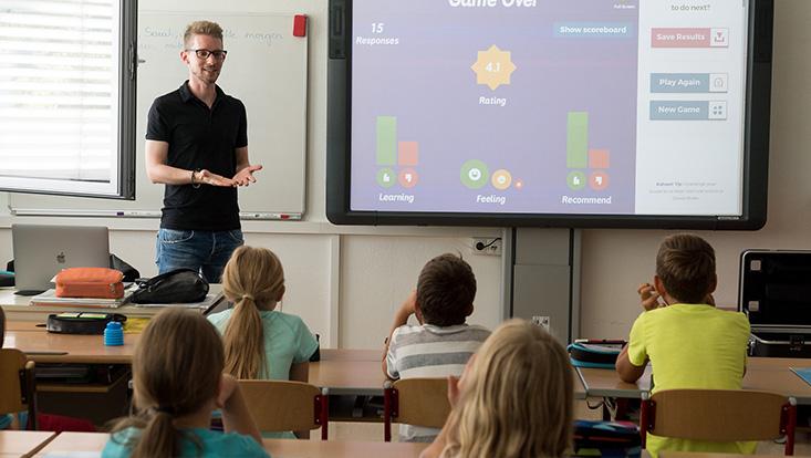 Schulklasse mit Reihenanordnung der Tische, Frontalunterricht (mit Smartboard).